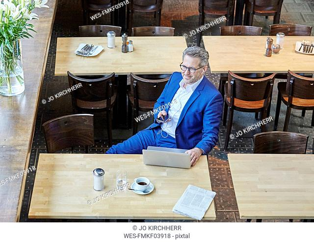 Mature businessman in cafe with laptop, cell phone and earbuds