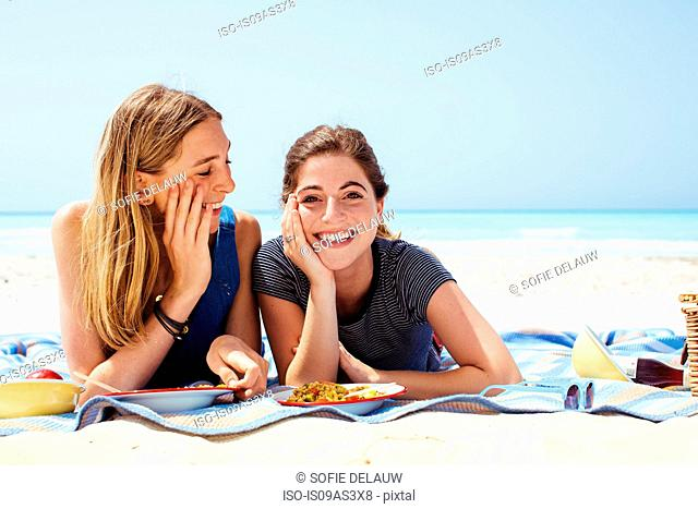 Portrait of two young female friends lying on picnic blanket at beach