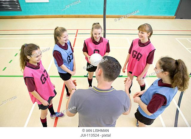Gym teacher teaching high school students netball in gym class