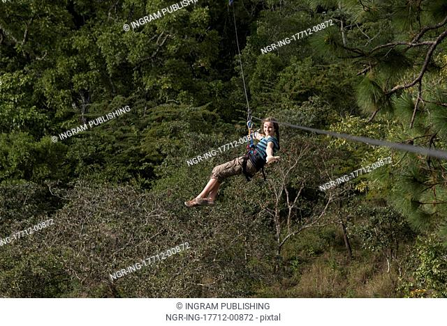 Girl riding a zip line in a forest, Copan, Copan Ruinas, Copan Department, Honduras