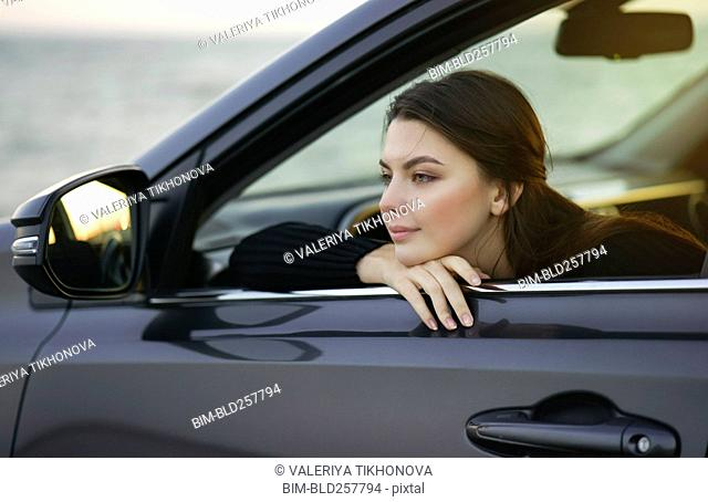 Pensive Caucasian woman leaning in car window