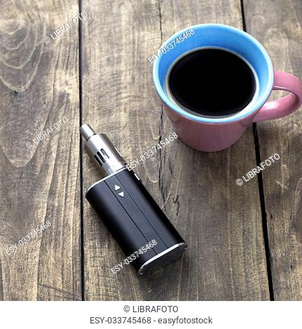 e-cigarette and cup of coffee on table, from above