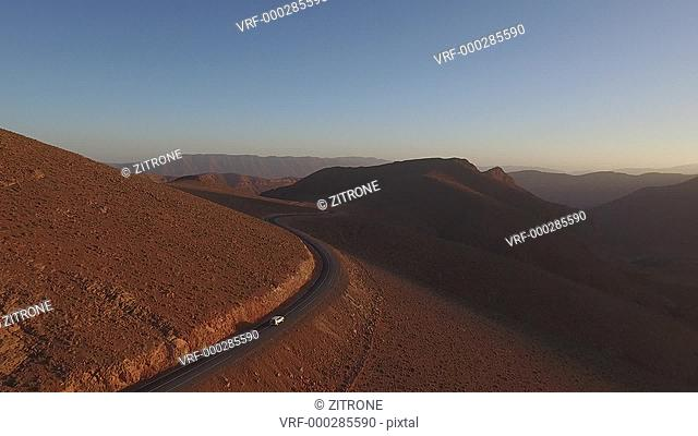 Drone footage of car moving on winding road amidst arid landscape during sunset, High Atlas, Morocco