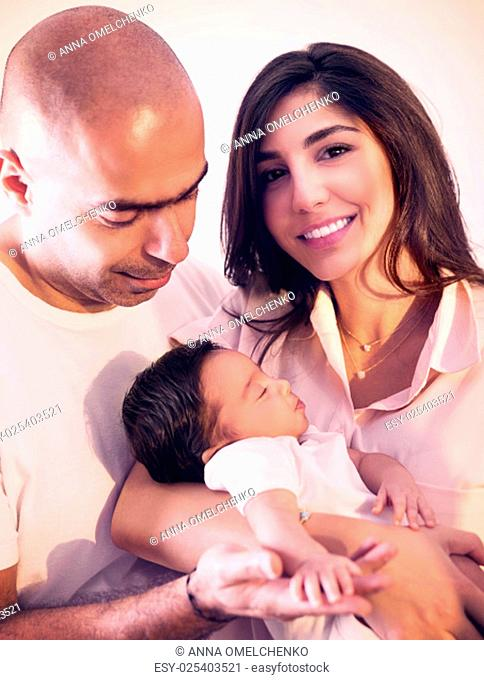 Portrait of cheerful mother and father holding on hands cute sleeping newborn baby, spending time at home, happy young family, love and happiness concept