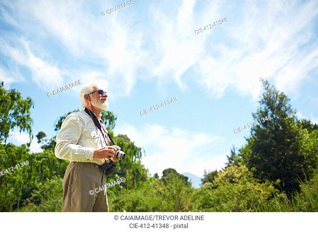 Curious active senior man with digital camera looking up at sunny trees and sky