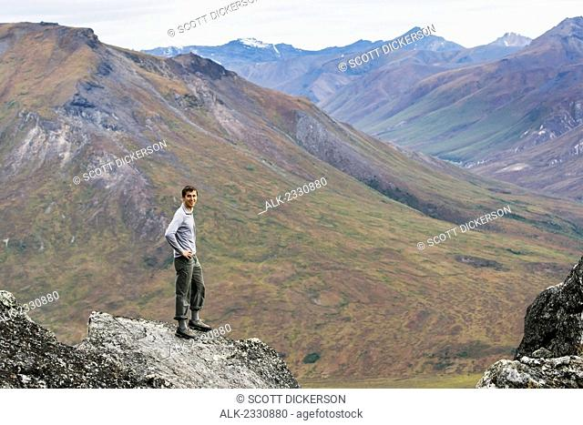 Hiker on ridge above Noatak River in Brooks Range, Gates of the Arctic National Park, Northwestern Alaska, above the Arctic Circle, Arctic Alaska, summer