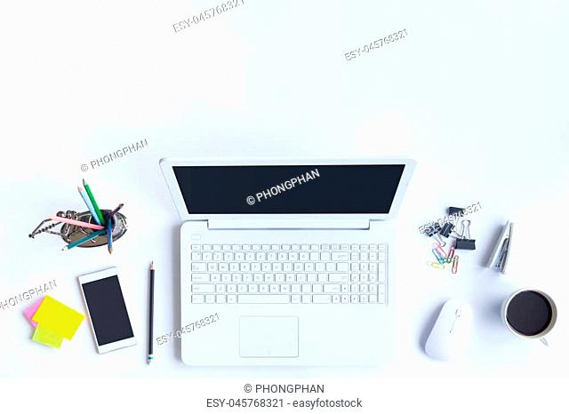 White desk office with laptop, smartphone and other work supplies with cup of coffee. Top view with copy space for input the text