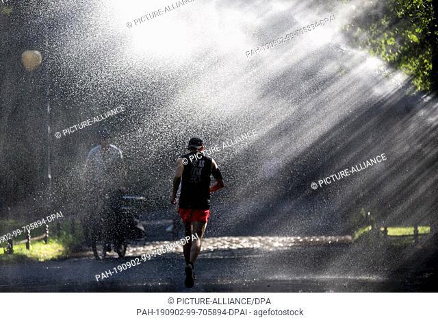 02 September 2019, Berlin: A jogger runs through the sunlit water jet of an irrigation system in Berlin's Tiergarten. Photo: Christoph Soeder/dpa