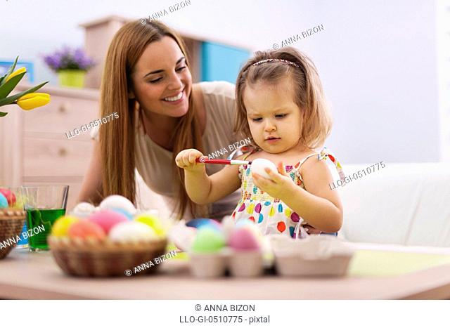 Family playing during painting easter eggs. Debica, Poland&#10