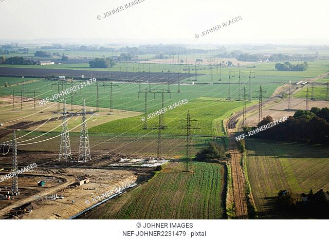 Aerial view of electricity pylons on fields