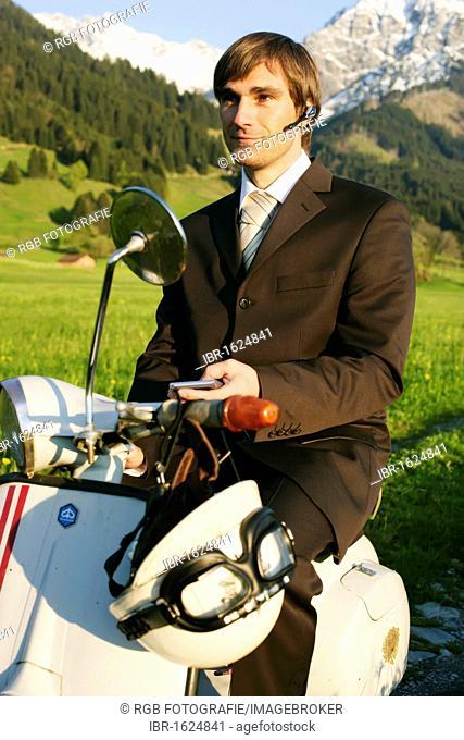 Businessman, 29, on a classic motor scooter, Allgaeu, Bavaria, Germany, Europe