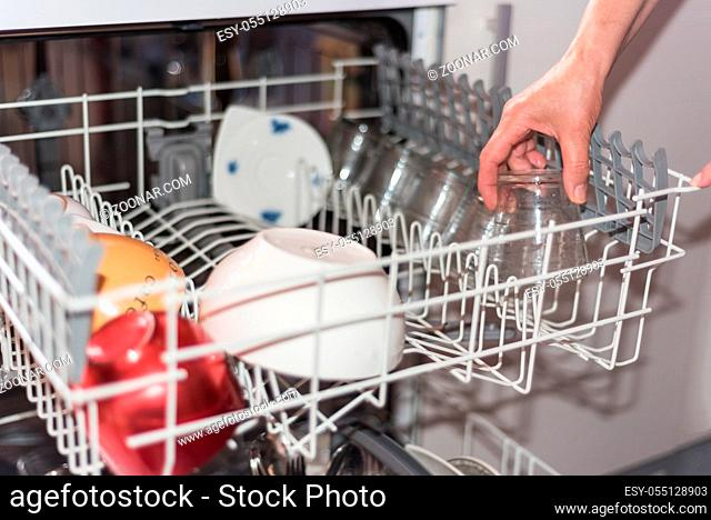 Close up view of a woman?s hand loading the dishwasher. Shallow dof, selective focus on the hand