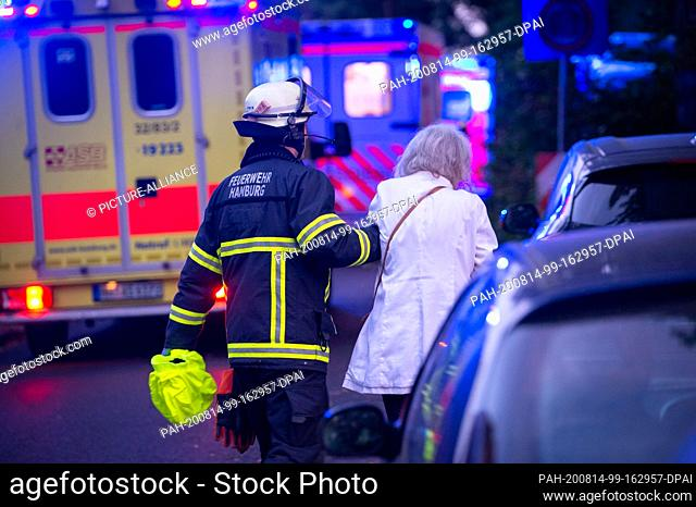 14 August 2020, Hamburg: A fireman leads an evacuated resident past ambulances. Six people were slightly injured in a fire in a retirement home