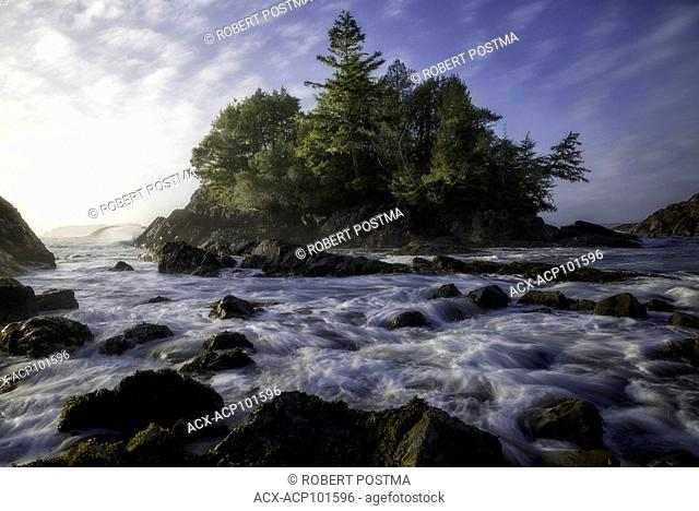 Late day sun hitting an island while waves crash over the rocks at high tide, Tofino, British Columbia, Canada