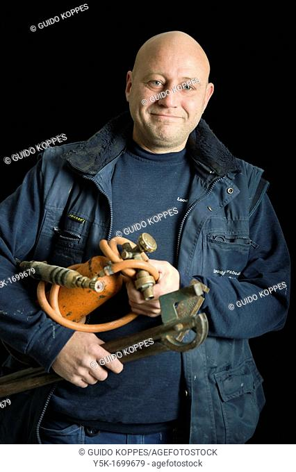 Portrait of a plumber, with his torch, in front of a black background. Photograph - portrait taken during the reconstruction of a bathroom