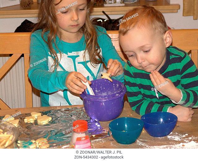 Kinder helfen der Mutter beim Weihnachtsplätzchen backen