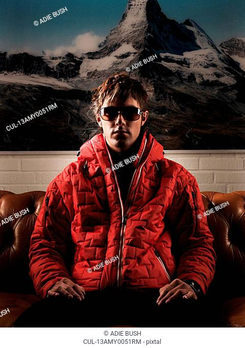 Man in red jacket sitting on couch