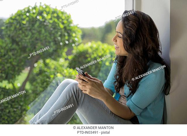 India, Woman looking through window with mobile phone in hands