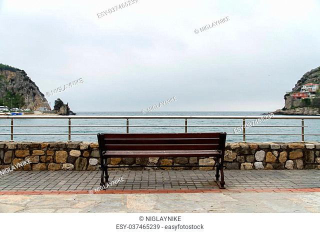Empty wooden bench at seascape, cloudy weather