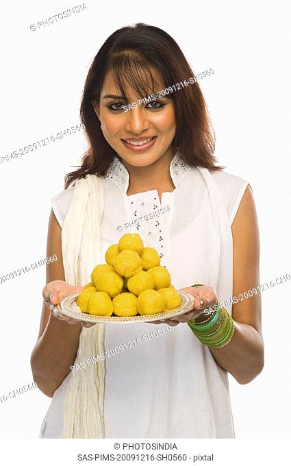 Woman holding Laddu in a plate on Holi