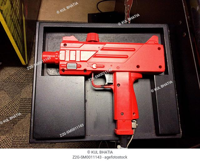 A red plastic gun used to fire fake bullets in a video game, Canada