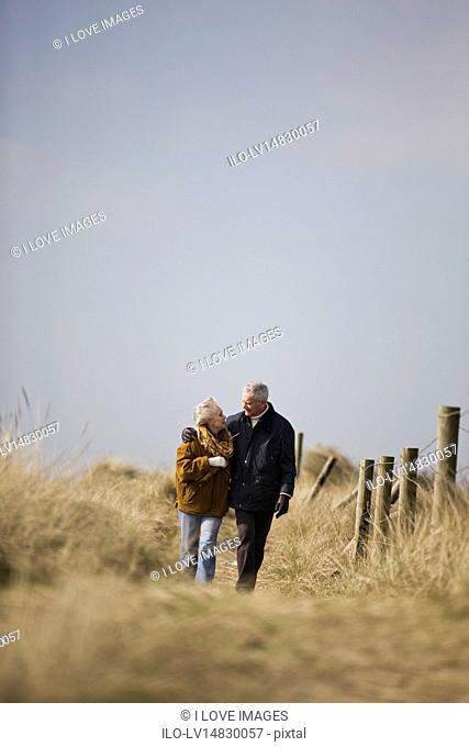A senior couple walking along a path together