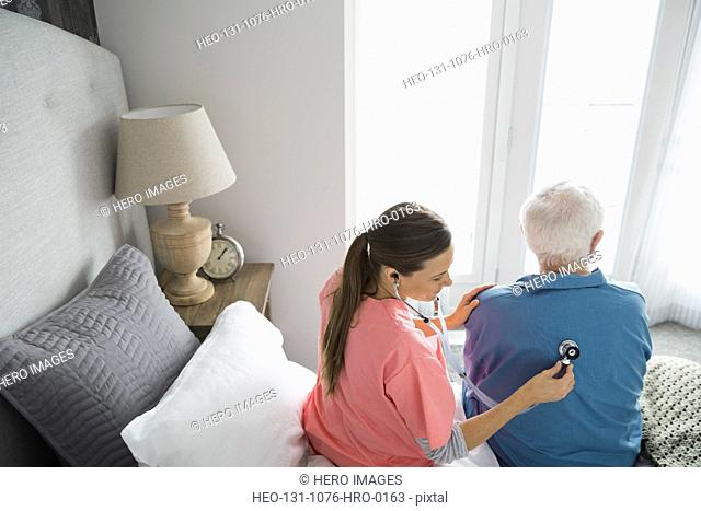 Home care nurse examining man with stethoscope