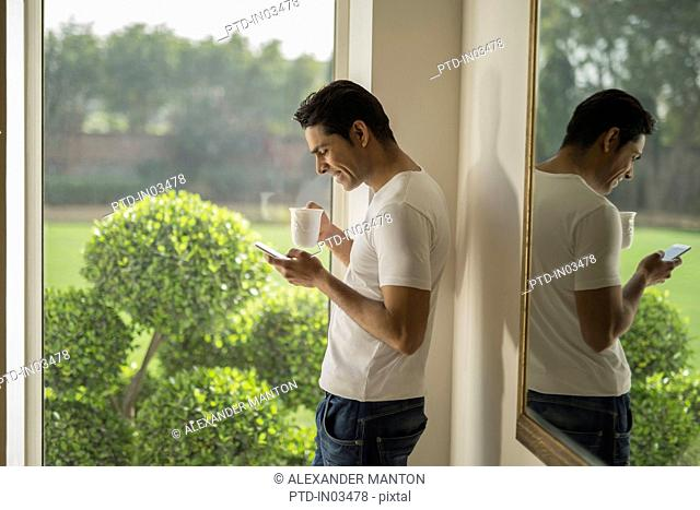 India, Man at window using mobile phone and holding coffee cup