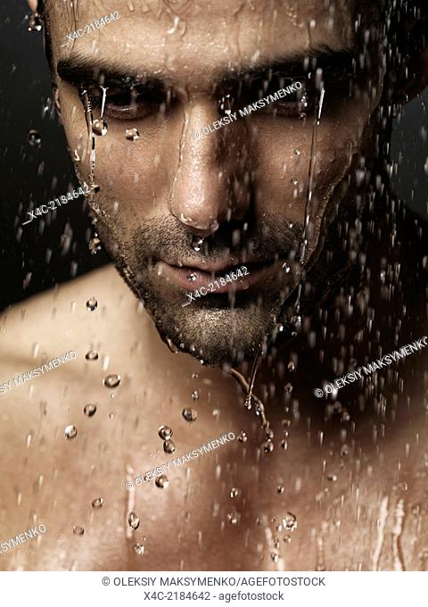 Thoughtful man face with his eyes down wet from shower water pouring on it, dramatic emotional portrait