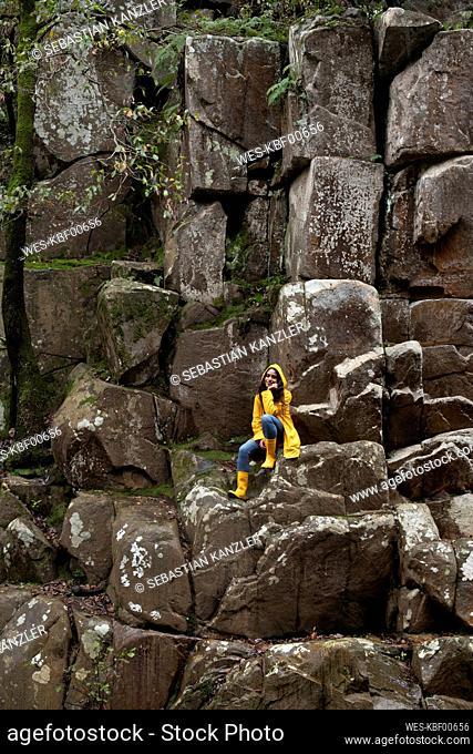 Female hiker wearing yellow raincoat sitting on rocks in forest