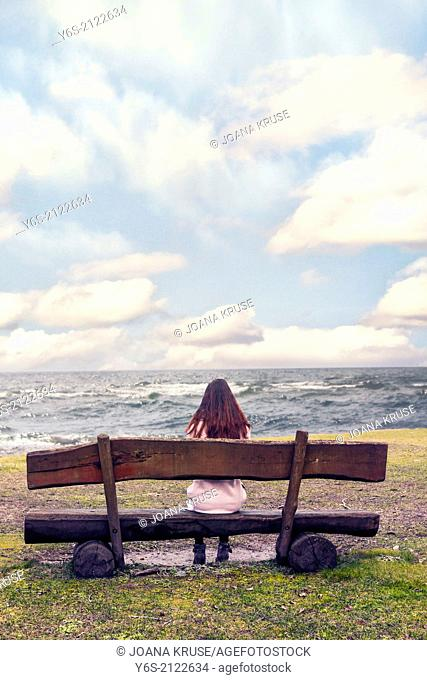 a woman is sitting on a bench at the sea