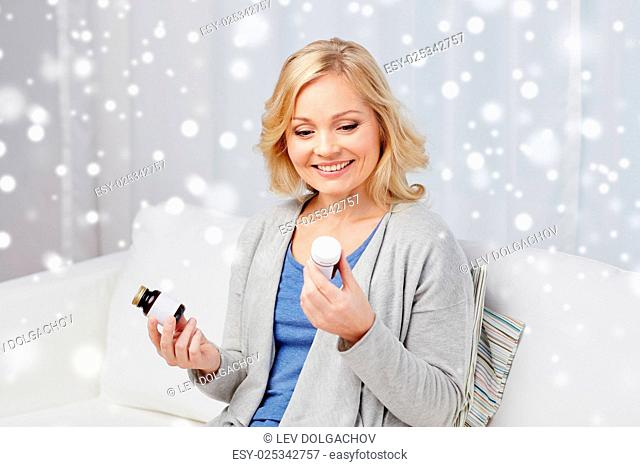medicine, healthcare and people concept - woman looking at jars with medication at home over snow