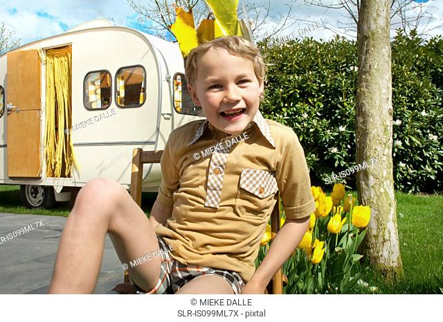 Boy sitting outside caravan wearing party hat