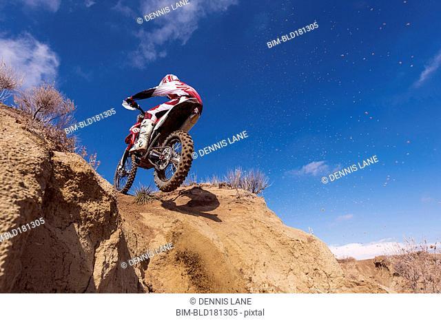 Motorcyclist riding dirt bike on hillside