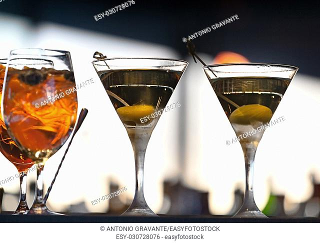 Two glasses of alcoholic drinks with olive