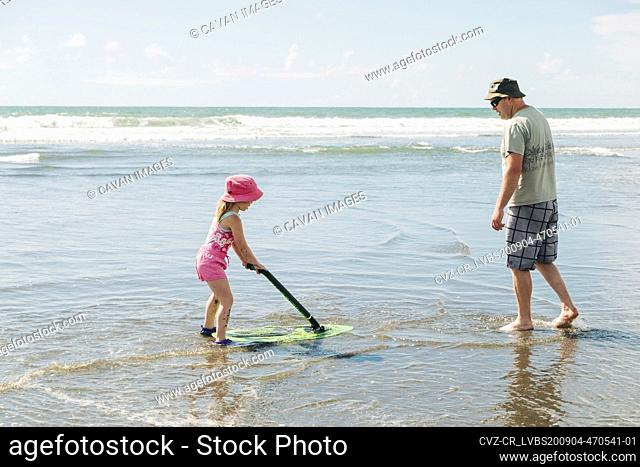 Young girl and her father playing on the beach with a skim board