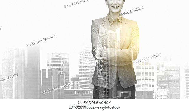 business, people and corporate concept - smiling businesswoman over city buildings background and double exposure effect