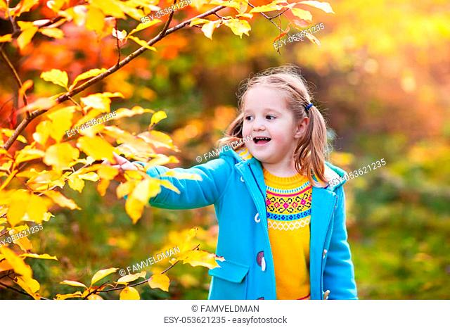 Kids play in autumn park. Children throwing yellow and red leaves. Little girl with oak and maple leaf. Fall foliage. Family outdoor fun in autumn