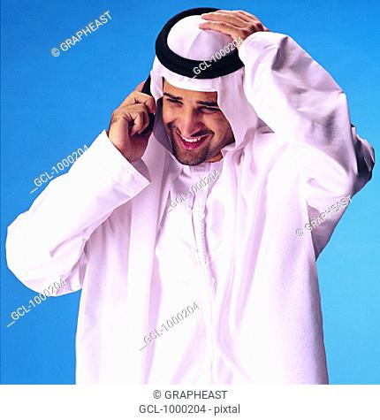 Arab man holding his head while speaking on cell phone