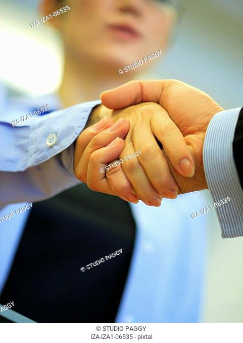 Close-up of a businesswoman and a businessman shaking hands
