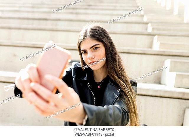 Young woman on stairs taking a selfie