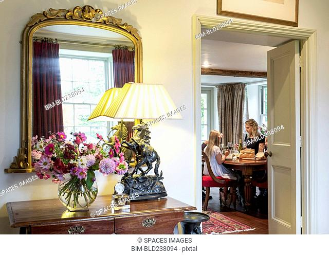 Doorway to Caucasian mother and daughter eating in dining room