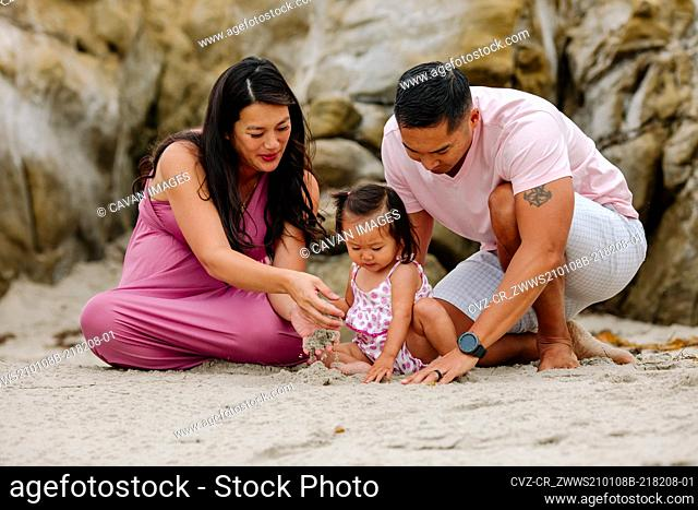 Expectant Asian parents playing in sand at beach with young daughter