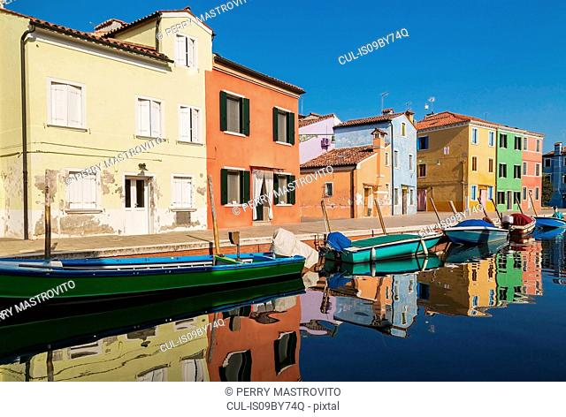 Moored green and blue boats on canal lined with colourful stucco houses, Burano Island, Venetian Lagoon, Venice, Veneto, Italy