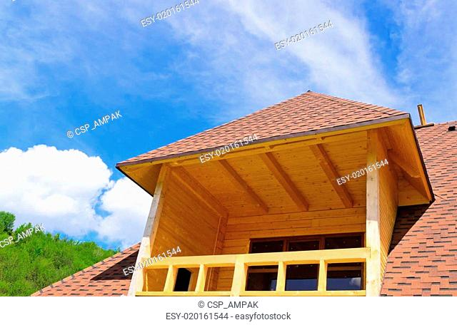 Dormer with a balcony on top of a house