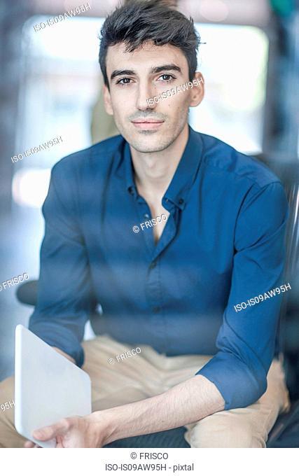 Portrait of young businessman holding digital tablet