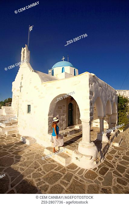 Tourist woman in front of the blue domed main church in Parikia, Paros, Cyclades Islands, Greek Islands, Greece, Europe