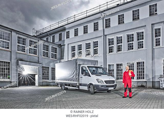 Man standing next to delivery van on yard of a building