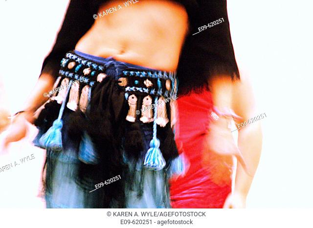 torso and arms of slim belly dancer, another dancer's torso partially visible in background