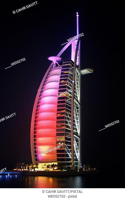 The 7 star luxury Burj al Arab Hotel by night, seen from the grounds of the 5 Star luxury Jumeirah Beach Resort Hotel at Jumeirah Beach, Dubai